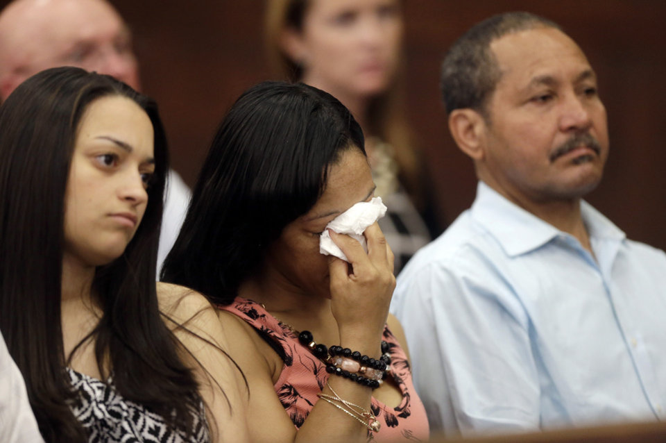 Photo - A woman wipes her eyes, center, while sitting next to Ernesto Abreu, right, father of shooting victim Daniel de Abreu, during a hearing for former New England Patriots football player AaronHernandez in Suffolk Superior Court, Tuesday, June 24, 2014, in Boston. Prosecutors allege that Hernandez ambushed and shot to death two men, Daniel de Abreu and Safiro Furtado, in 2012 after a chance encounter inside a Boston nightclub. Hernandez has pleaded not guilty. (AP Photo/Steven Senne, Pool)