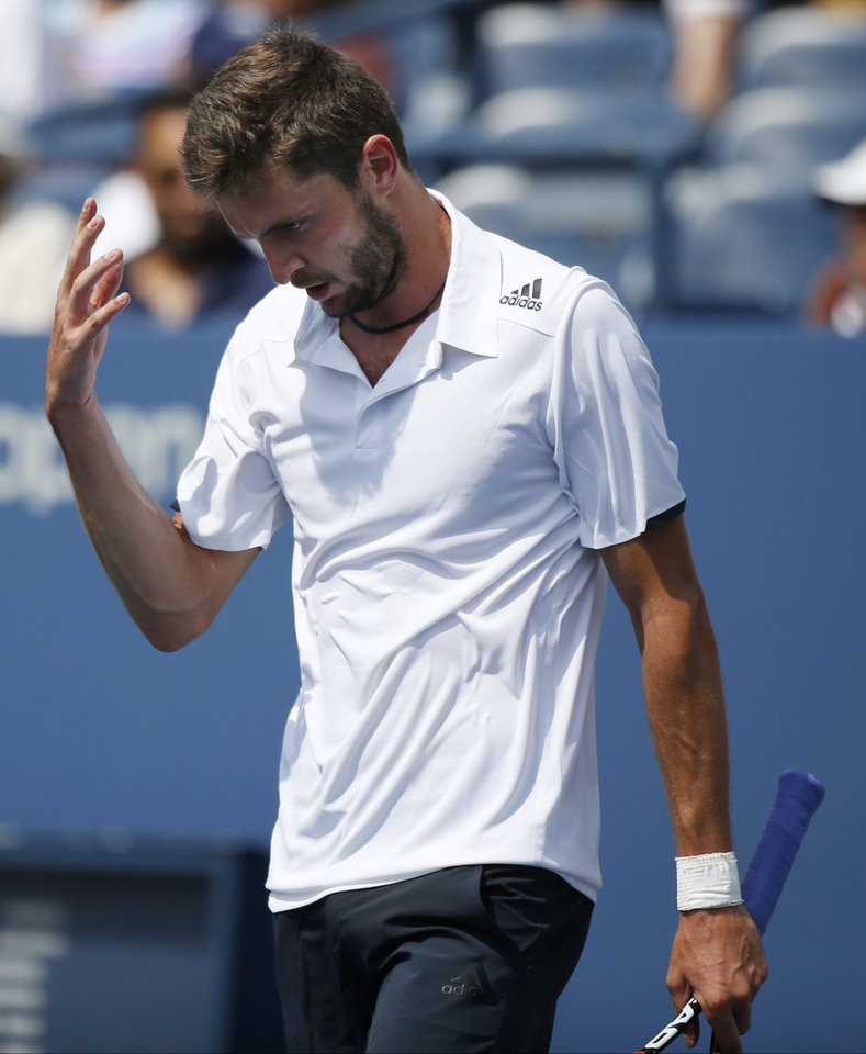 Photo - Gilles Simon, of France, reacts after a shot against David Ferrer, of Spain, during the third round of the 2014 U.S. Open tennis tournament, Sunday, Aug. 31, 2014, in New York. (AP Photo/Seth Wenig)