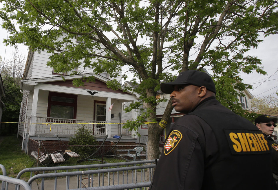 Photo - A sheriff deputy stands outside a house where three women escaped Tuesday, May 7, 2013, in Cleveland. Three women who went missing separately about a decade ago were found in the home Monday just south of downtown and likely had been tied up during years of captivity, said police, who arrested three brothers. (AP Photo/Tony Dejak)