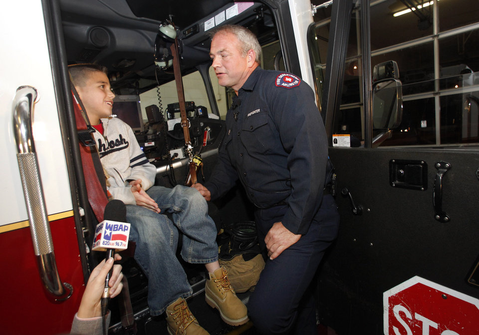 Koregan Quintanilla, 10, of Watauga, Texas, left, talks to firefighter Wesley Keck as they prepare to take a short trip around the neighborhood on a fire truck Thursday, Nov. 15, 2012, in Arlington, Texas. Quintanilla, who was abandoned at a fire station as an infant, celebrated his recent birthday by meeting Keck, the firefighter who saved him, riding on a fire truck and touring the station. (AP Photo/Tony Gutierrez)