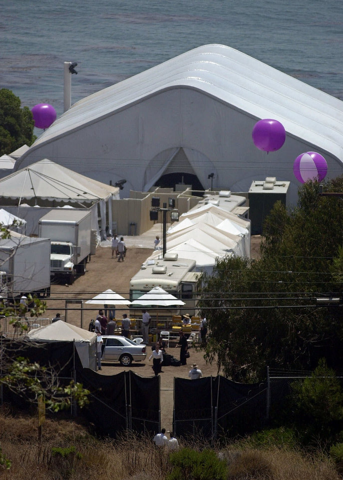 Photo - FILE - In this July 29, 2000 file photo, security and caterers set up for the oceanside wedding of Brad Pitt and Jennifer Aniston in Malibu, Calif. In contrast to Brangelina's smallish, tight-as-a-drum ceremony, Pitt's last wedding to Aniston was huge and over the top. The $1 million ceremony in 2000 included a 40-piece gospel choir, floating lotus flowers, a 13-minute fireworks display and imported candles from Thailand. (AP Photo/Mark J. Terrill, file)