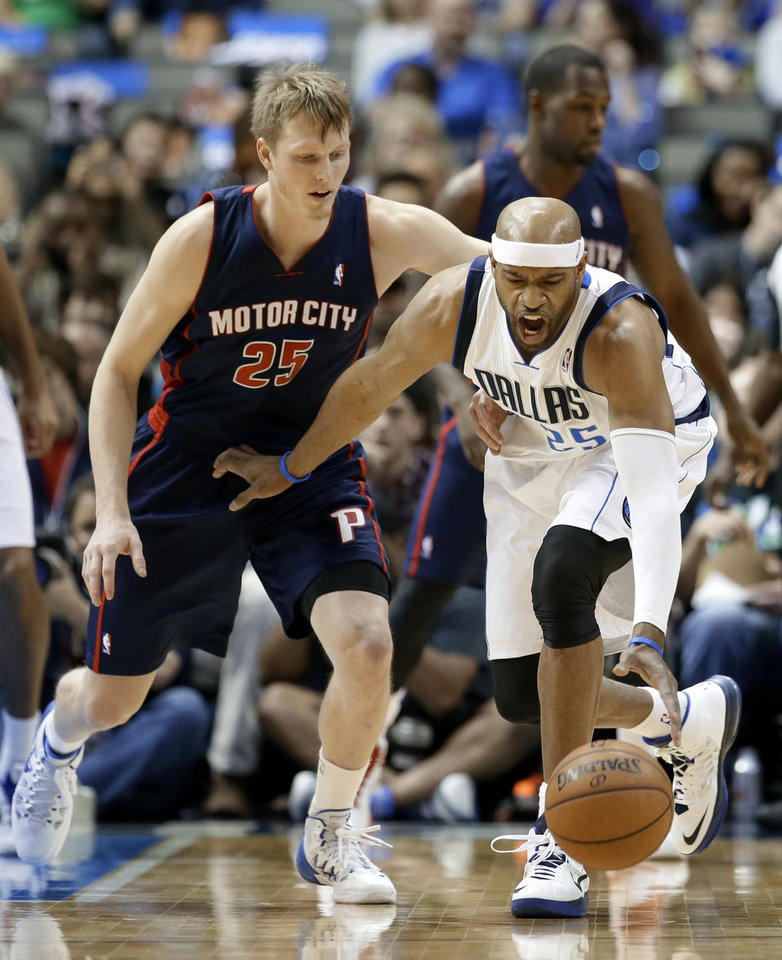 Photo - Dallas Mavericks shooting guard Vince Carter (25) reaches down to grab a loose ball in front of Detroit Pistons' Kyle Singler (25) in the first half of an NBA basketball game, Sunday, Jan. 26, 2014, in Dallas. (AP Photo/Tony Gutierrez)