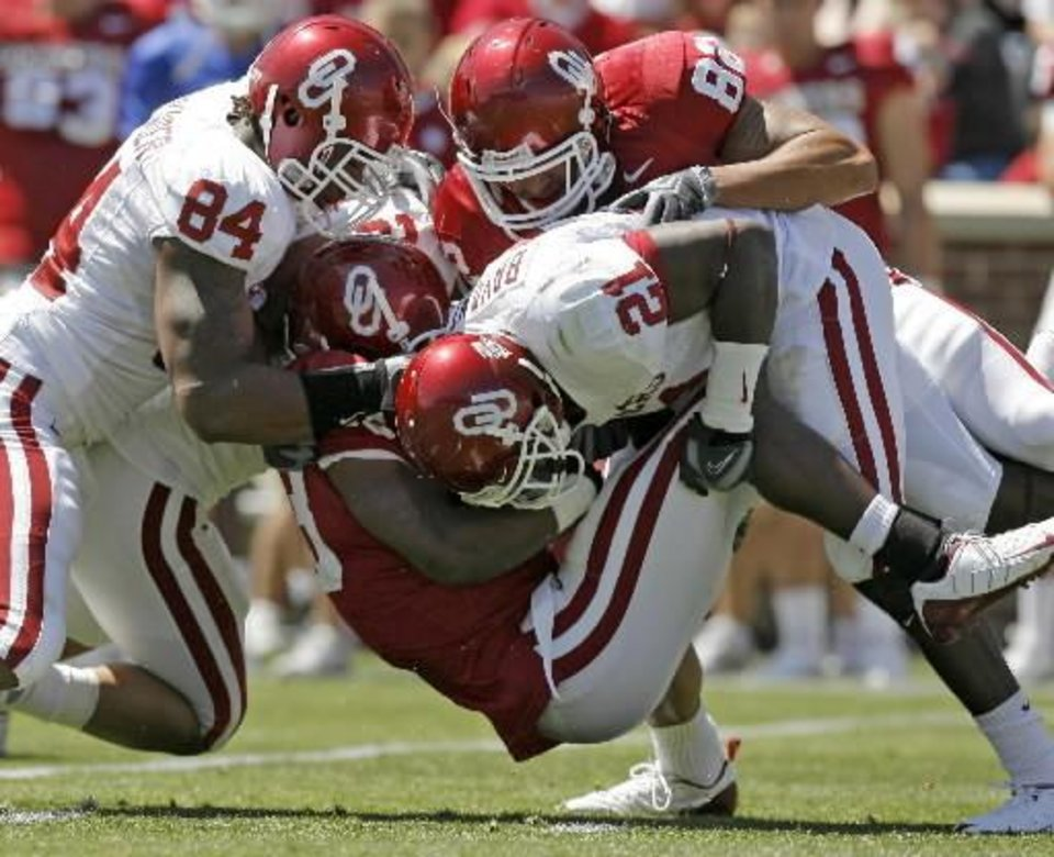OU's Jermie Calhoun is brought down by Frank Alexander, left, and J.R, Bryant as James Hanna falls on top of the pile during the University of Oklahoma's Red-White college  football game at The Gaylord Family -- Oklahoma Memorial Stadium in Norman, Okla., Saturday, April 11, 2009. Photo by Bryan Terry