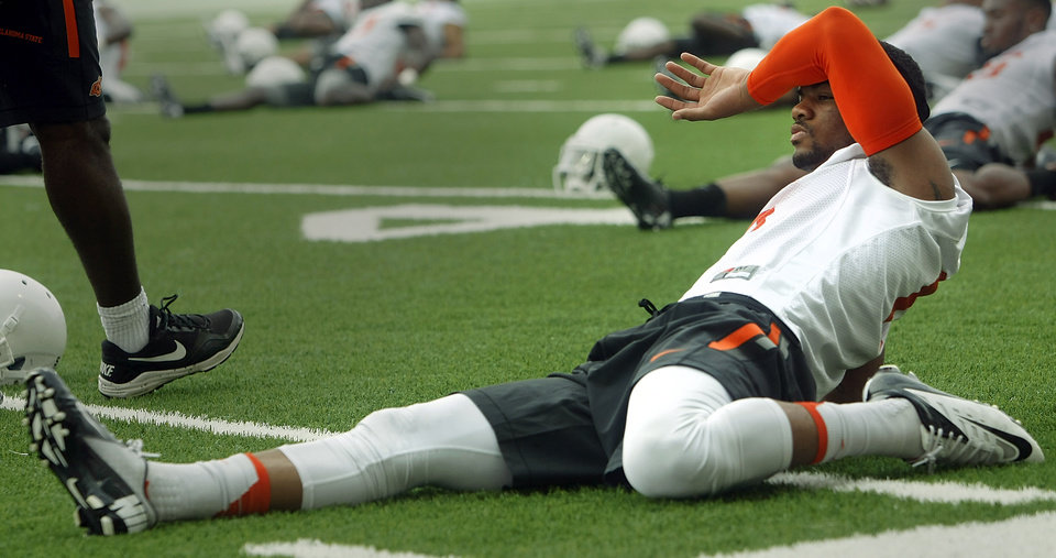 Photo - Oklahoma State corner Ashton Lampkin (6) stretches during the first team practice of the fall at the Sherman E. Smith Training Facility on the campus of Oklahoma State University in Stillwater on August 1, 2014. Photo by KT King, The Oklahoman