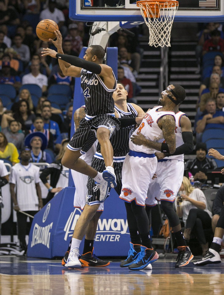 Photo - Orlando Magic's Arron Afflalo (4) passes the ball while guarded by New York Knicks' J.R. Smith (8) during overtime of an NBA basketball game in Orlando, Fla., Friday, Feb. 21, 2014. The Magic won 129-121 in two overtimes. (AP Photo/Willie J. Allen Jr.)
