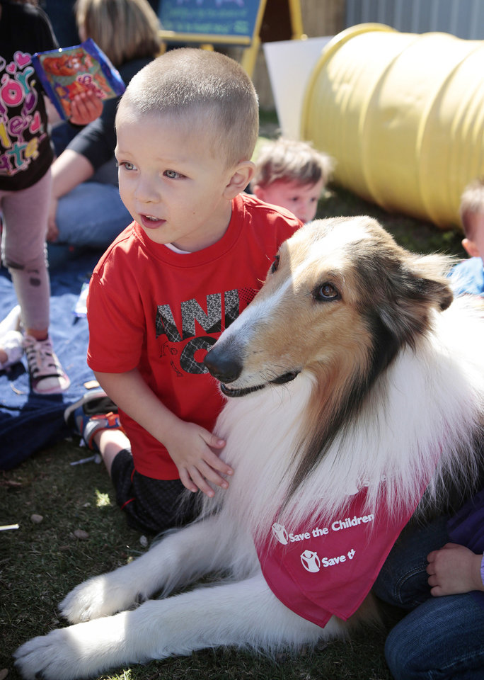 Avery Rios, 3, of Moore, pets Lassie, the new Save The Children ambassador, during the groundbreaking ceremony of a new storm shelter at Agapeland Learning Center in Moore. Photo Provided PROVIDED