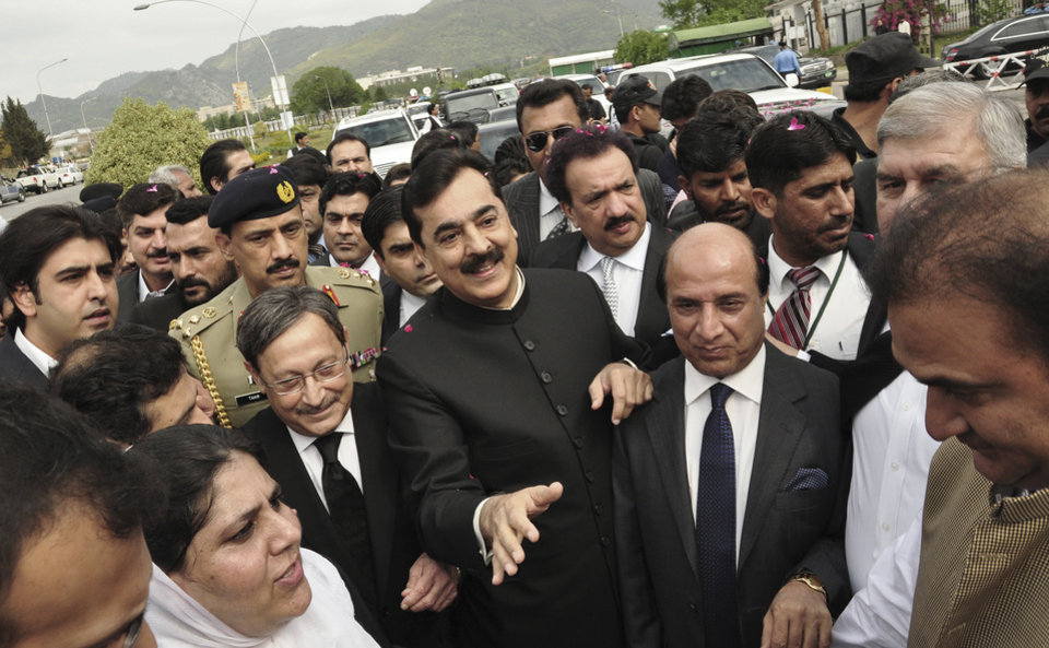 Photo -   Pakistani Prime Minister Yousuf Raza Gilani, center, makes his way to the Supreme Court for a hearing in Islamabad, Pakistan, Thursday, April 26, 2012. The Supreme Court convicted Gilani of contempt on Thursday for refusing to reopen an old corruption case against President Asif Ali Zardari on Thursday, but spared him a prison term in a case that has stoked political tensions in the country.(AP Photo/B.K. Bangash)
