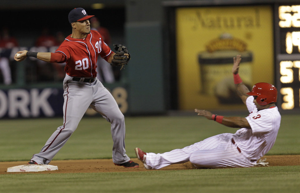 Photo - Philadelphia Phillies' Marlon Byrd, right, is out at second on a hit by Domonic Brown as Washington Nationals' Ian Desmond throws to first in the fifth inning of a baseball game on Saturday, May 3, 2014, in Philadelphia. (AP Photo/Laurence Kesterson)