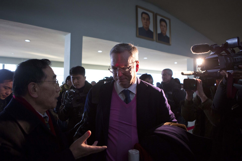 Google Chief Executive Eric Schmidt, center, is surrounded by journalists as he walks into the Pyongyang International Airport in Pyongyang, North Korea as he and former Governor of New Mexico Bill Richardson, unseen, depart for Beijing on Thursday, Jan. 10, 2013. (AP Photo/David Guttenfelder)