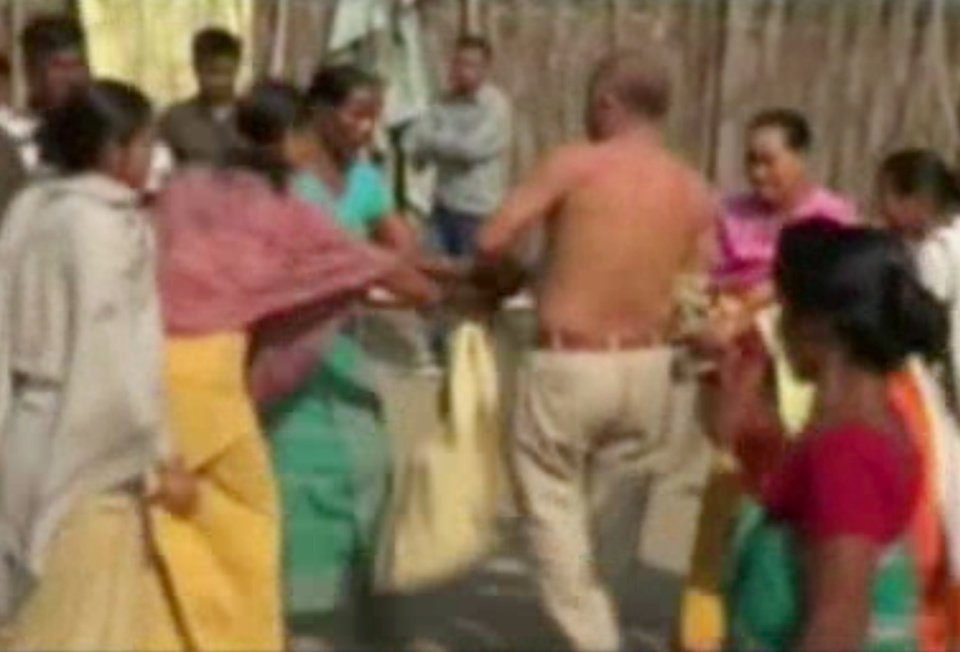 Photo - In this image taken from video obtained from Network 1 News and Information Syndicate (NNIS), which has been authenticated based on its contents and other AP reporting, Bikram Singh Brahma, center, a leader of India's ruling Congress party, has his shirt torn off by women in the village of Santipur, India, on Thursday, Jan. 3, 2013. Police said Brahma was visiting the village of Santipur on the Bhutan border when he entered a woman's house and raped her at 2 a.m. In a sign that attitudes might be changing since the rape of a 23-year-old woman in New Delhi, who died of severe internal injuries over the weekend, police have arrested Brahma. (AP Photo/NNIS)