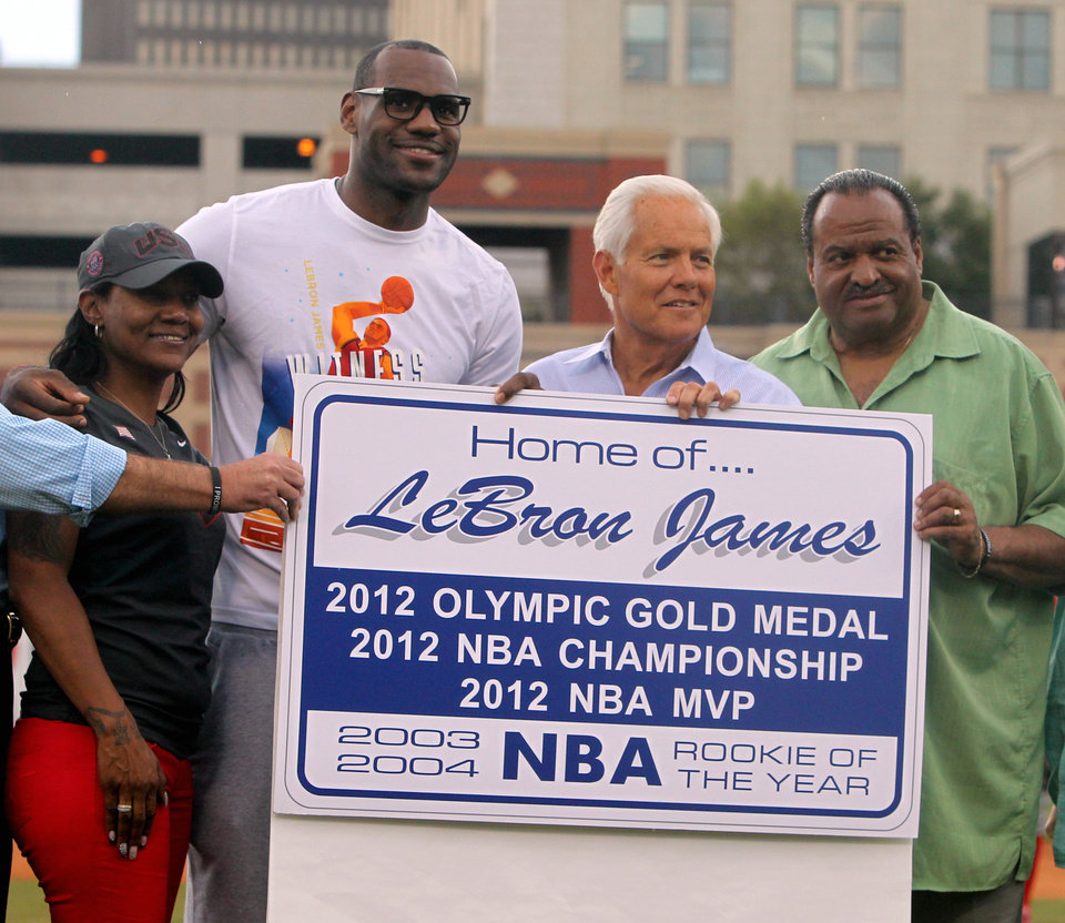 Photo -   ** ADDS MANDATORY CREDIT** NBA star and Akron native LeBron James poses with his mother Gloria James, left, Akron Mayor Don Plusquellic and Akron City Council president Marco Sommerville with a sign that will be placed at the borders to the city of Akron at Canal Park during an Akron Aeros game Sunday, Aug. 19, 2012 in Akron, Ohio.(AP Photo/Akron Beacon Journal, Karen Schiely) MANDATORY CREDIT