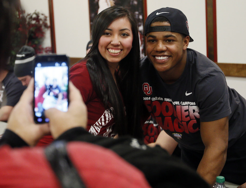 Photo - Alyssa Baker, 17, of Broken Bow, Okla., has her picture taken with OU football player Sterling Shepard during an autograph session for fans with the Sooner football team before an NCAA men's college basketball game between Baylor and the University of Oklahoma at Lloyd Noble Center in Norman, Okla., Saturday, Feb. 8, 2014. Photo by Nate Billings, The Oklahoman