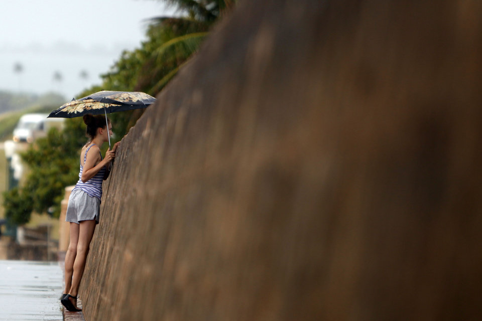 Photo - A woman looks over the seaside wall of the 16th century Spanish fort El Morro, under cloudy skies in San Juan, Puerto Rico, Saturday, Aug. 2, 2014. Bertha pushed just south of Puerto Rico on Saturday as it unleashed heavy rains and strong winds across the region. (AP Photo/Ricardo Arduengo)