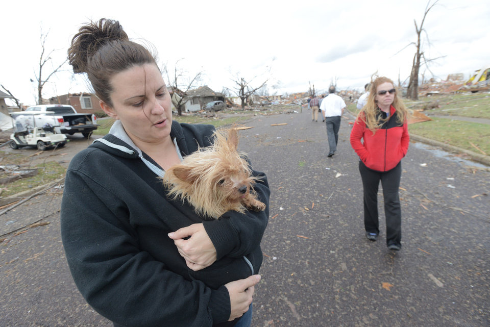 Photo - Aimee Royer holds a dog she rescued from debris after a Sunday morning tornado sliced through a subdivision on the North side of Washington, Ill., Sunday, Nov. 17, 2013. Royer and her friend, Kendra Gray, at right, said their home was spared. Several homes are cleared down to the foundation. Intense thunderstorms and tornadoes swept across the Midwest, causing extensive damage in several central Illinois communities while sending people to their basements for shelter. (AP Photo/The Pantagraph, Steve Smedley)