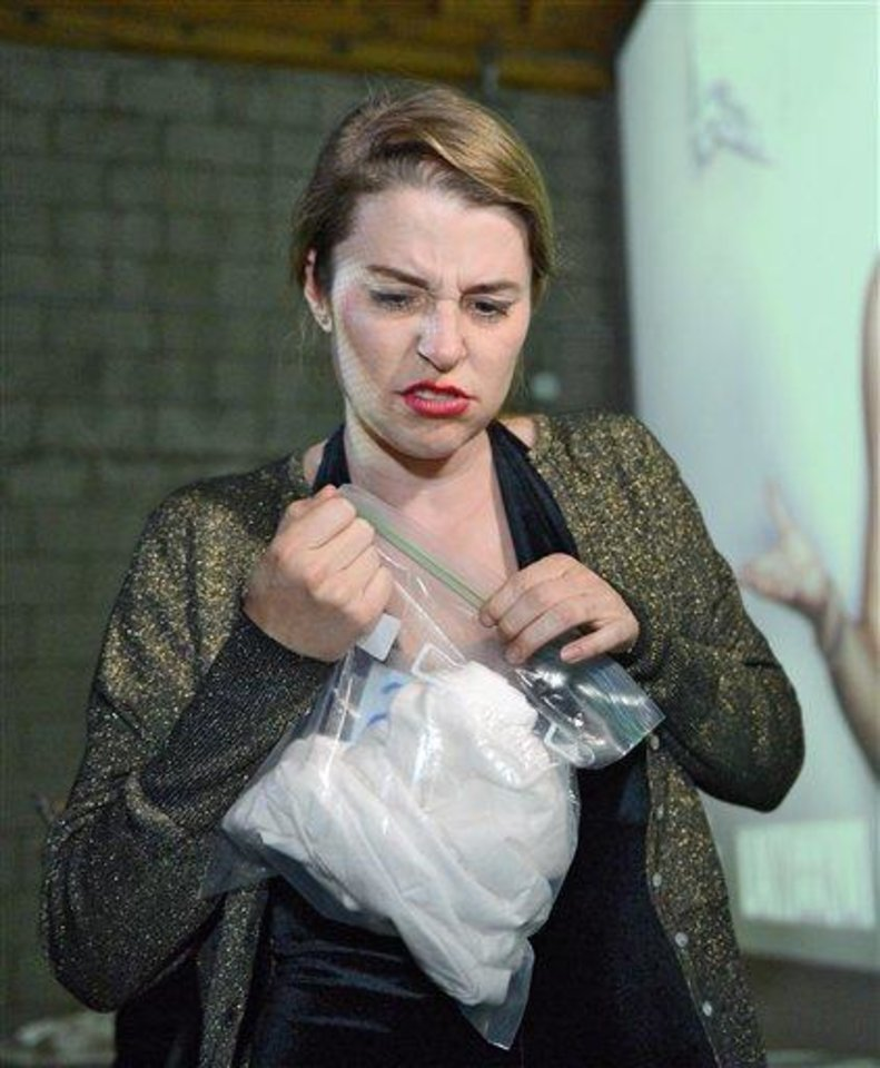 Photo - Tegan Artho-Bentz reacts after smelling a shirt during a pheromone party, Friday, June 15, 2012, in Los Angeles. The get-togethers, which have been held in New York and Los Angeles and are planned for other cities, require guests to submit a slept-in T-shirt that will be sniffed by other participants. Then you can pick your partner based on scent. (AP Photo/Mark J. Terrill)