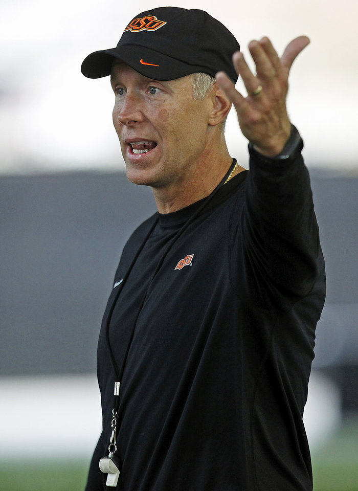 Photo - Oklahoma State offensive line Bob Connelly instructs the line during the first team practice of the fall at the Sherman E. Smith Training Facility on the campus of Oklahoma State University in Stillwater on August 1, 2014. Photo by KT King, The Oklahoman