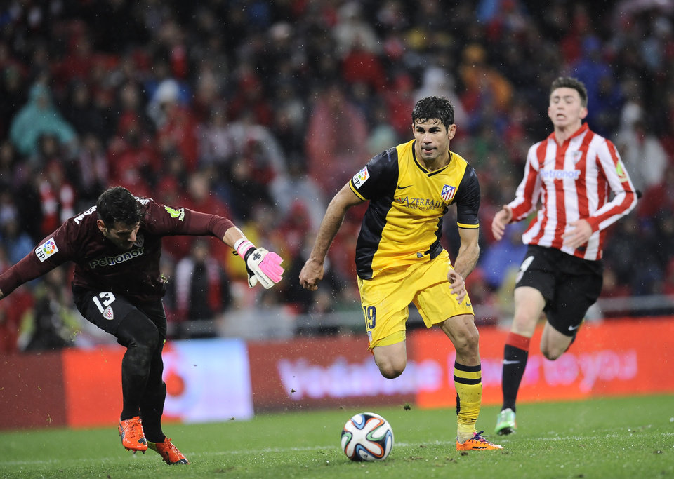 Photo - Atletico de Madrid's Diego Costa of Brazil, center, goes past goalkeeper Iago Herrerin to score his goal during their Spanish Copa del Rey round-8 second leg soccer match against Athletic Bilbao, at San Mames stadium, in Bilbao, northern Spain, Wednesday, Jan. 29, 2014. (AP Photo/Alvaro Barrientos)