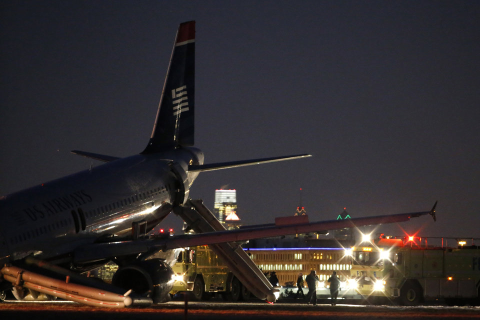 Photo - Investigators work near a damaged US Airways jet at the end of a runway at the Philadelphia International Airport, Thursday, March 13, 2014, in Philadelphia. Airline officials said the flight was heading to Fort Lauderdale, Fla., when the pilot was forced to abort takeoff around 6:30 p.m., after the front landing gear failed. An airport spokeswoman said no injuries have been reported. (AP Photo/Matt Slocum)