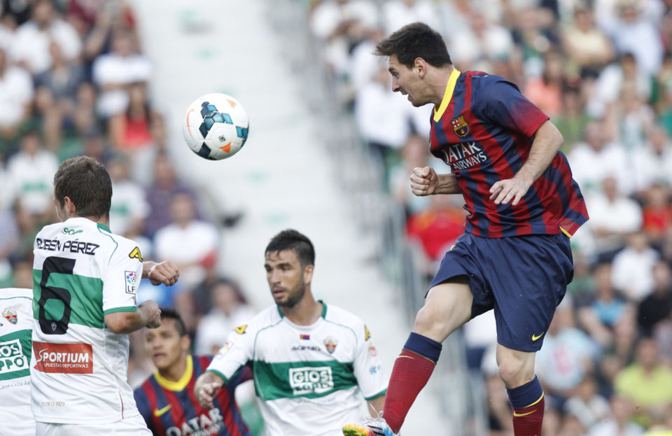 Photo - Barcelona's Lionel Messi from Argentina, right, heads the ball past Elche's Ruben Perez del Marmol during a Spanish La Liga soccer match at the Martinez Valero stadium in Elche, Spain, on Sunday, May 11, 2014.(AP Photo/Alberto Saiz)