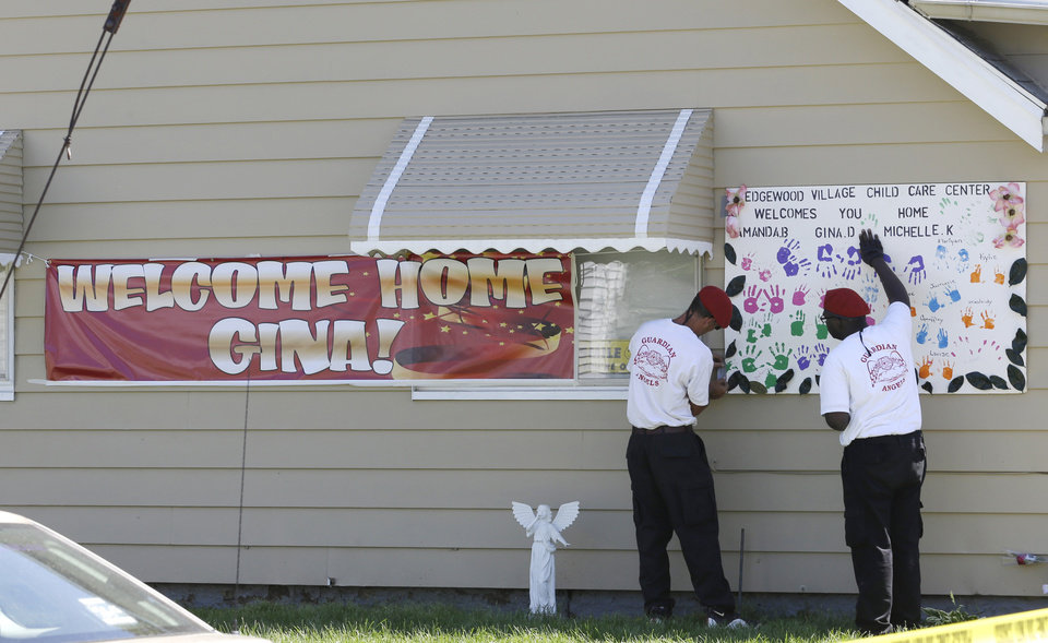 Photo - Two Gaurdian Angels hang a poster at the home of Gina DeJesus Thursday, May 9, 2013, in Cleveland. Ariel Castro, the man accused of raping and kidnapping DeJesus and two other women, who were missing for about a decade before being found alive at his home, was ordered held Thursday on $8 million bail. (AP Photo/Tony Dejak)