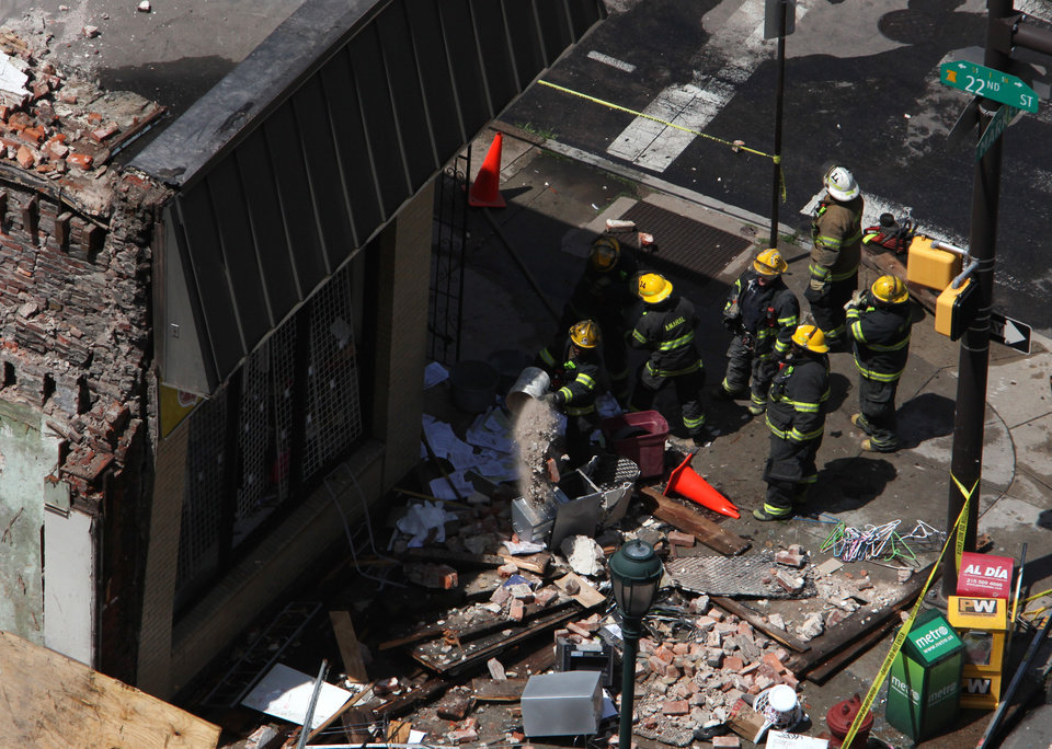 Photo - Rescue personnel removed debris from the area of a collapsed building in downtown Philadelphia Wednesday June 5, 2013.  A four-story building being demolished collapsed Wednesday on the edge of downtown, injuring 12 people and trapping two others, the fire commissioner said.   (AP Photo/Jacqueline Larma)