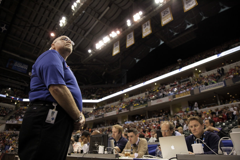 Photo - In this photo taken on March 16, 2014, Bill Hefler, of ESG Security, looks up to the stands during a time out in the second half of an NCAA college basketball game between Ohio State and Michigan in the semifinals of the Big Ten Conference tournament in Indianapolis. Security firms charged with protecting college and professional sports venues are monitoring social media more than ever to prepare for everything from a garden-variety court storming to something much more dangerous. (AP Photo/Kiichiro Sato)