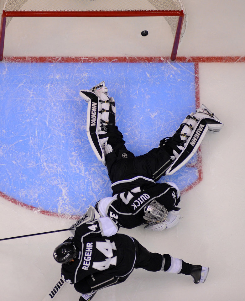Photo - Los Angeles Kings goalie Jonathan Quick, top, is scored on by San Jose Sharks left wing Matt Nieto as defenseman Robyn Regehr, of Brazil, looks on during the second period in Game 3 of an NHL hockey first-round playoff series , Tuesday, April 22, 2014, in Los Angeles. (AP Photo/Mark J. Terrill)