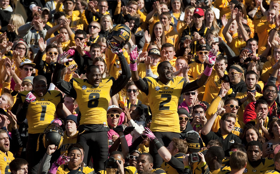 Photo -  Missouri's L'Damian Washington, right, Darius White, center, and John Gibson, left, celebrate with fans after they defeated Florida 36-17 in an NCAA college football game Saturday, Oct. 19, 2013, in Columbia, Mo. (AP Photo/L.G. Patterson)