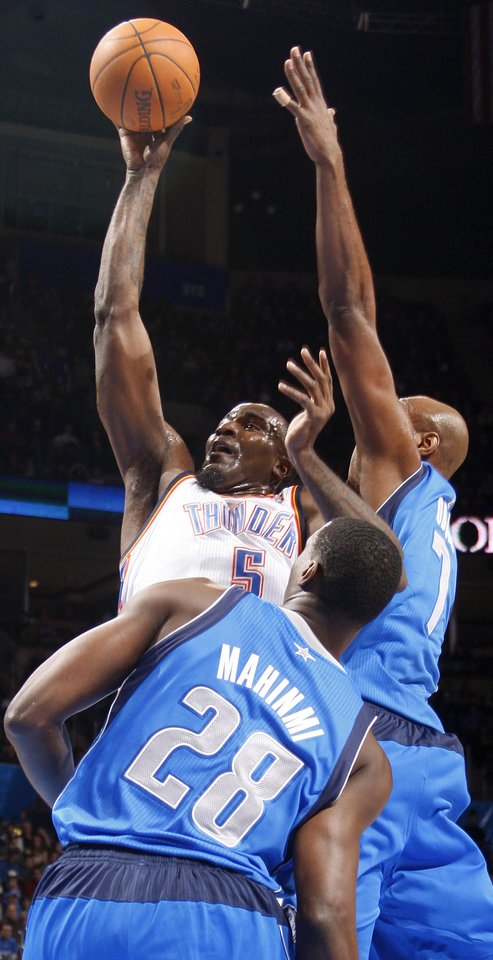 Photo - Oklahoma City's' Kendrick Perkins (5) shoots the ball between Dallas' Ian Mahinmi (28) and Lamar Odom (7) during a preseason NBA game between the Oklahoma City Thunder and the Dallas Mavericks at Chesapeake Energy Arena in Oklahoma City, Tuesday, Dec. 20, 2011. Photo by Bryan Terry, The Oklahoman
