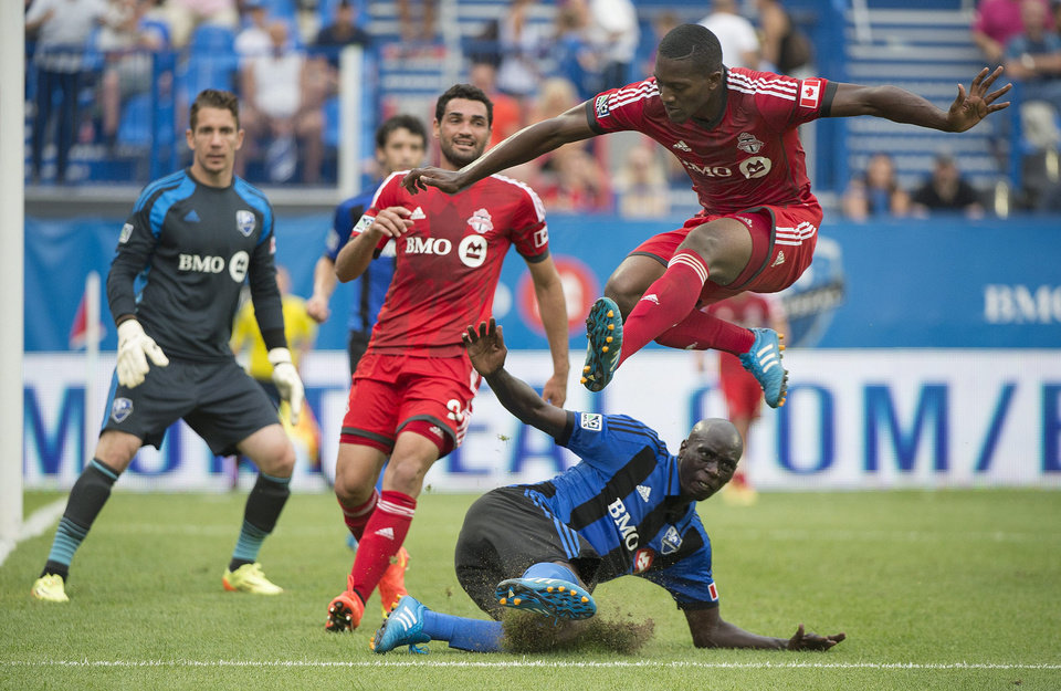 Photo - Toronto FC's Doneil Henry leaps over Montreal Impact's Hassoun Camara, as Impact's goalkeeper Troy Perkins, left, and Toronto's Gilberto look on during the second half of a soccer match in Montreal, Saturday, Aug. 2, 2014. (AP Photo/The Canadian Press, Graham Hughes)