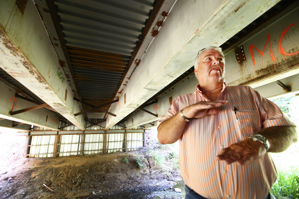 Photo - McClain County District 2 Commissioner Wilson Lyles stands under a bridge near Washington, OK, that used steel beams from the old Interstate 40 Crosstown Expressway.  David McDaniel - THE OKLAHOMAN
