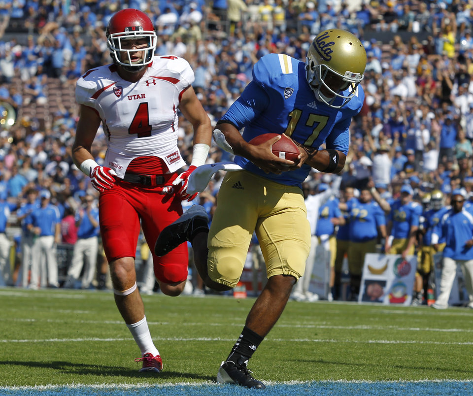 UCLA quarterback Brett Hundley, right, runs in for a 12-yard touchdown with Utah defensive back Brian Blechen, left, in pursuit during the first half of their NCAA college football game, Saturday, Oct. 13, 2012, in Pasadena, Calif. (AP Photo/Alex Gallardo)