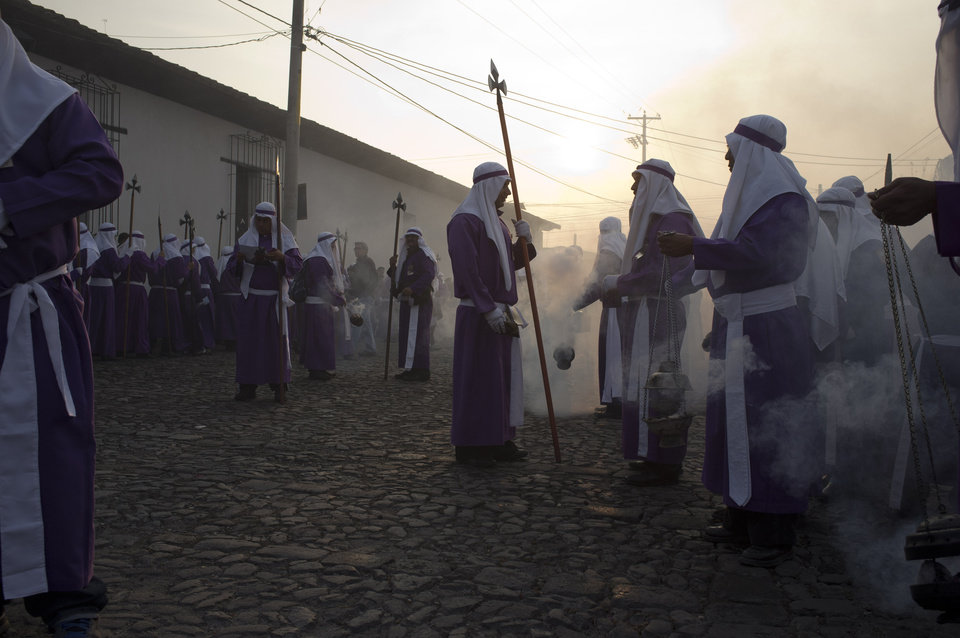 Photo - Penitents burn incense as they take part in a procession by La Merced church as part of Holy Week celebrations in Antigua Guatemala, Friday, April 18, 2014. Holy Week commemorates the last week of the earthly life of Jesus Christ culminating in his crucifixion on Good Friday and his resurrection on Easter Sunday. (AP Photo/Moises Castillo)