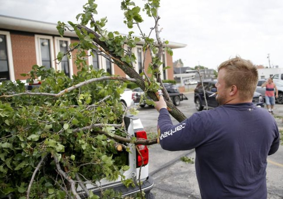 Photo -  Heath Wright helps clear tree damage from the Trinity Baptist Church parking lot in Oklahoma City on Sunday. Wright lives in a nearby neighborhood and volunteered to help the church. [Sarah Phipps/The Oklahoman]