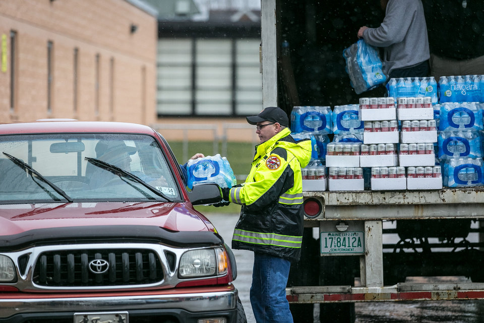 Photo - Members of the Nitro Volunteer Fire Department distribute water to local residents following the chemical spill on Friday, Jan. 10, 2014 in Charleston, W.V. About 300,000 people in nine counties entered their third day Saturday without being able to drink, bathe in, or wash dishes or clothes with their tap water after a foaming agent escaped the Freedom Industries plant in Charleston and seeped into the Elk River.  (AP Photo Michael Switzer)