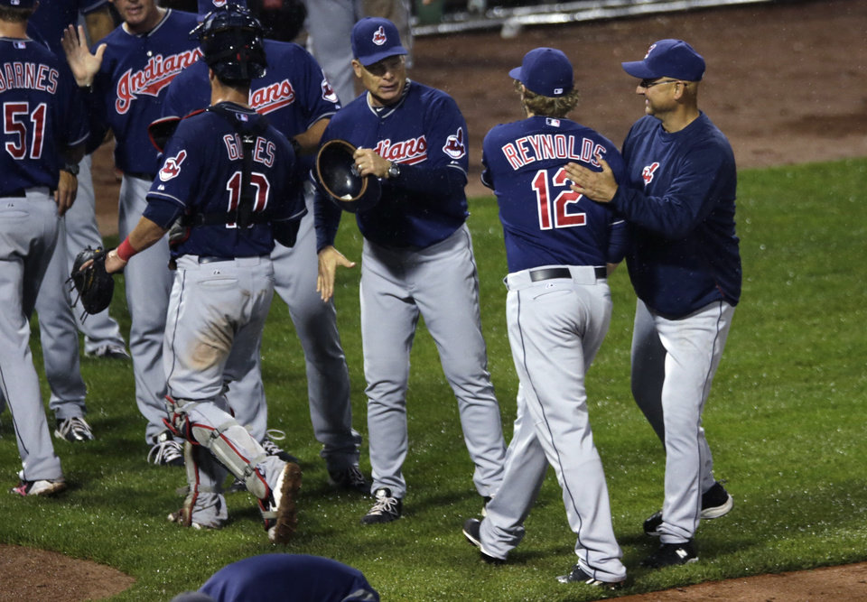 Photo - Cleveland Indians manager Terry Francona, right, gives designated hitter Mark Reynolds (12) a pat on the back after defeating the Boston Red Sox during a baseball game at Fenway Park in Boston, Thursday, May 23, 2013. The Indians won 12-3. (AP Photo/Charles Krupa)