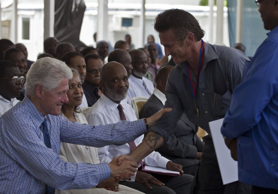 Photo -   FILE - In this Monday, July 12, 2010 file photo, former U.S. President and U.N. special envoy for Haiti, Bill Clinton, left, shakes hands with U.S. actor Sean Penn after Penn received a medal for the assistance provided to Haiti during a memorial ceremony at the National Palace on the six-month anniversary of the Jan. 12, 2010 earthquake in Port-au-Prince, Haiti. Seated at center is President Rene Preval. The actor who stormed onto the scene of one of the worst natural disasters in history two years ago has certainly not lost interest. Defying skeptics, he has put down roots in Haiti, a country he hadn't even visited before the January 2010 earthquake, and has become a major figure in the effort to rebuild. (AP Photo/Ramon Espinosa)