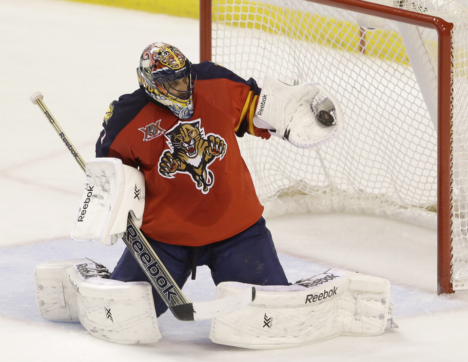 Photo - Florida Panthers goalie Roberto Luongo makes a save during the third period of an NHL hockey game against the Ottawa Senators, Tuesday, March 25, 2014 in Sunrise, Fla. Luongo made 37 saves as the Panthers defeated the Senators 3-2 in a shootout. (AP Photo/Wilfredo Lee)