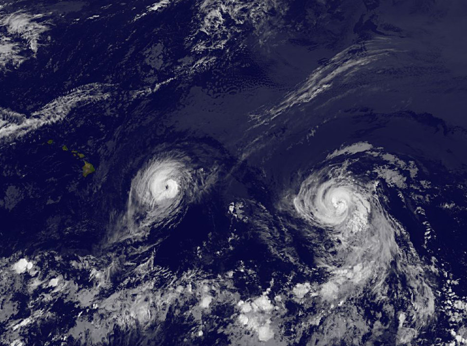 This image provided by NOAA taken Thursday Aug. 7, 2014 at 2 a.m. EDT shows Hurricane Iselle, left and Hurricane Julio. Iselle was supposed to weaken as it slowly trudged west across the Pacific. It didn\'t _ and now Hawaii is poised to take its first direct hurricane hit in 22 years. The center of Hurricane Iselle is expected to pass very near or over the Big Island Thursday night and just south of the smaller islands Friday. Some weakening is forecast during the next 48 hours however Iselle is still expected to be near hurricane strength as it impacts the Big Island. (AP Photo/NOAA)