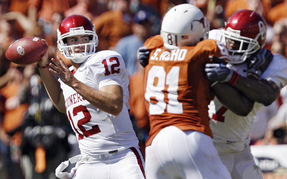 Photo - Oklahoma's Landry Jones (12) gets protection as he looks to throw the ball during the Red River Rivalry college football game between the University of Oklahoma Sooners (OU) and the University of Texas Longhorns (UT) at the Cotton Bowl in Dallas, Texas, Saturday, Oct. 17, 2009. Photo by Chris Landsberger, The Oklahoman