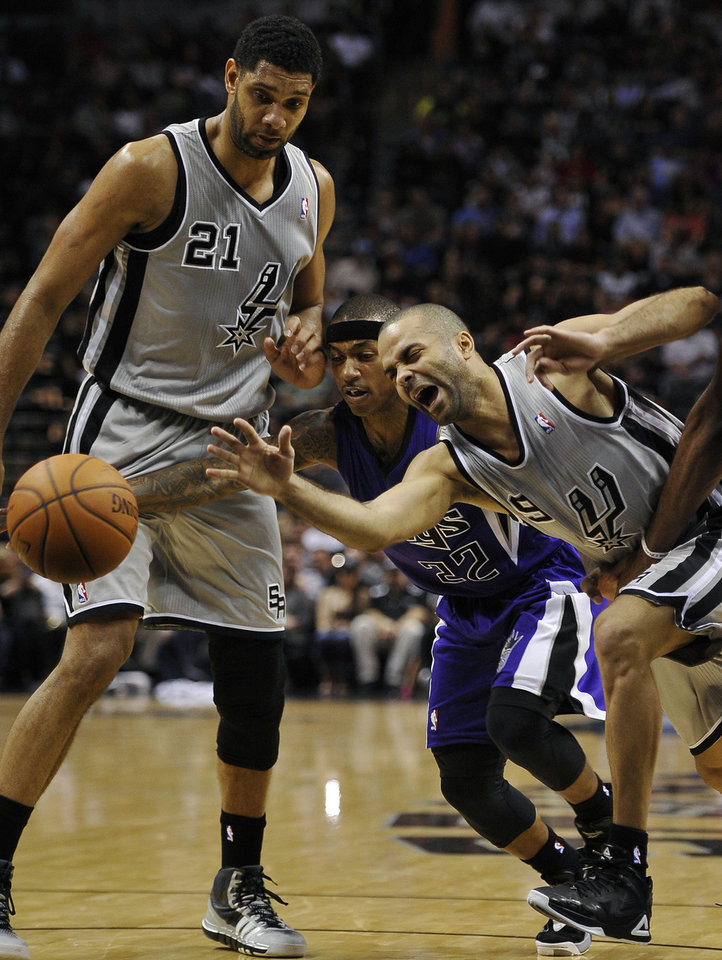 Photo - San Antonio Spurs guard Tony Parker, right, of France, falls as he drives past Sacramento Kings guard Isaiah Thomas, center, and Spurs forward Tim Duncan, during the first half of an NBA basketball game, Saturday, Feb. 1, 2014, in San Antonio. (AP Photo/Darren Abate)