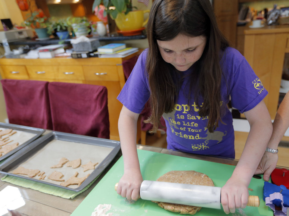 Rachel Rose uses a rolling pin as she  creates dog treats in her Oklahoma City home.  <strong>SARAH PHIPPS - SARAH PHIPPS</strong>