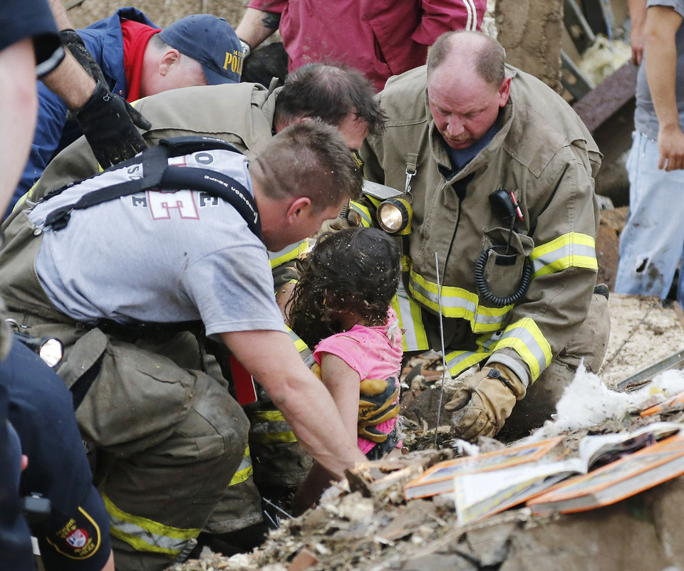 A child is pulled from beneath a collapsed wall at the Plaza Towers Elementary School in following a tornado in Moore, Okla., Monday, May 20, 2013. (AP Photo Sue Ogrocki) ORG XMIT: OKSO127