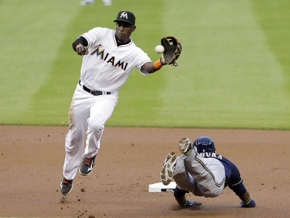 Photo - Milwaukee Brewers' Jean Segura, right, steals second base as Miami Marlins shortstop Adeiny Hechavarria is unable to catch the throw in the first inning of a baseball game in Miami, Friday, May 23, 2014. (AP Photo/Alan Diaz)