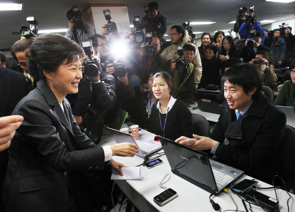 Photo - South Korea's president-elected Park Geun-hye, left, greets reporters after a press conference at the headquarters of Saenuri Party in Seoul, South Korea, Thursday, Dec. 20, 2012. Park was elected South Korean president Wednesday, becoming the country's first female leader despite the incumbent's unpopularity and her own past as the daughter of a divisive dictator. (AP Photo/Ahn Young-joon)