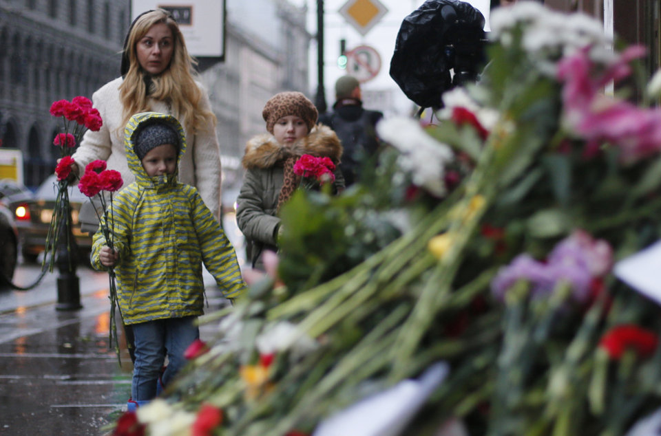 Photo - People lay flowers in front of the French consulate in St.Petersburg, Russia, Saturday, Nov. 14, 2015, for the victims of the Paris attacks on Friday. French President Francois Hollande said more than 120 people died Friday night in shootings at Paris cafes, suicide bombings near France's national stadium and a hostage-taking slaughter inside a concert hall. (AP Photo/Dmitry Lovetsky)