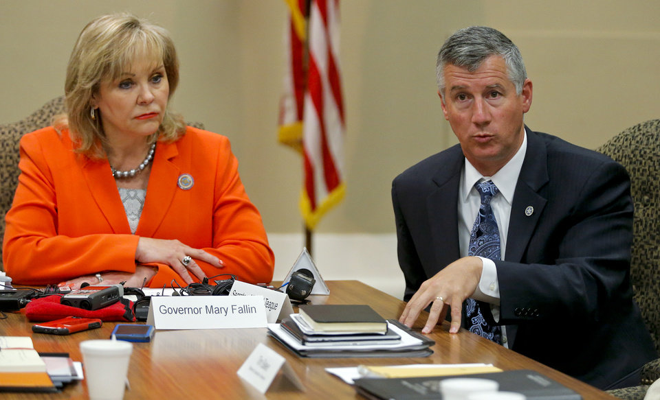 Photo - Gov. Mary Fallin looks on as Energy and Environment Secretary Michael Teague speaks during a press conference after a meeting of the Coordinating Council on seismic activity at the state Capitol on Tuesday, Aug. 4, 2015, in Oklahoma City, Okla. Photo by Chris Landsberger, The Oklahoman