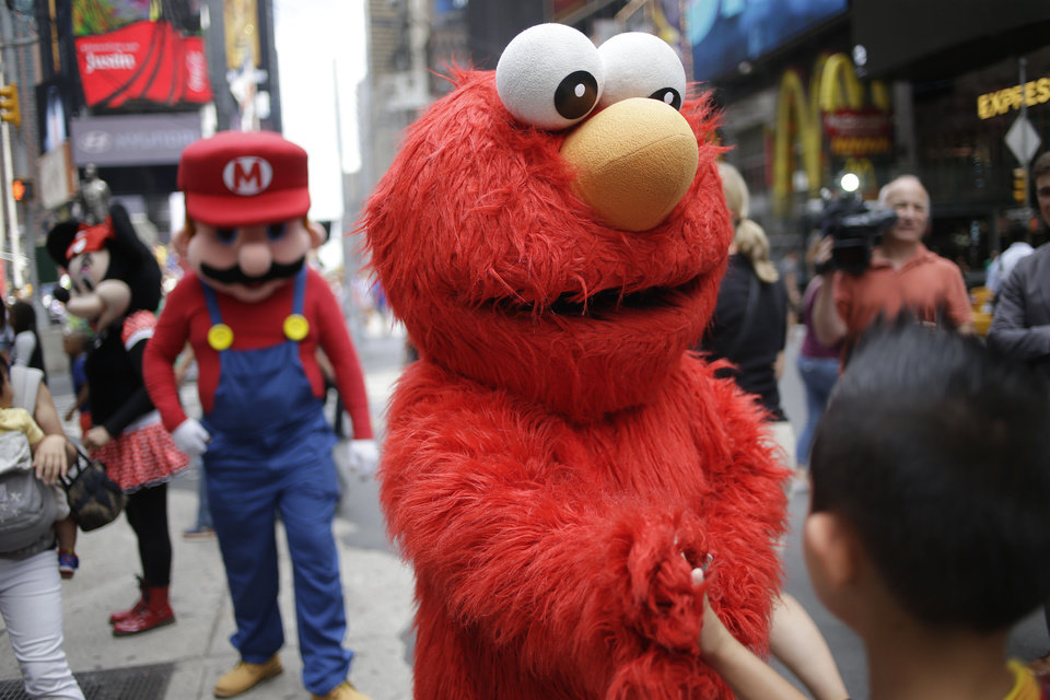 "Photo - A person dressed as Elmo shakes hands with a pedestrian in Times Square on Monday, July 28, 2014 in New York. New York City Mayor Bill de Blasio said Monday that he believes the people wearing character costumes in Times Square should be licensed and regulated. Dozens of people dressed as kids' favorites like Elmo, Cookie Monster and Batman stand near 42nd Street and pose for photos with tourists in exchange for money. De Blasio said the practice has ""gone too far.""  A man dressed as Spider-man was arrested Saturday, July 28, 2014, after punching a police officer who told him to stop harassing tourists.  The City Council is working on legislation that would require the characters to get a city-approved license.  (AP Photo/Seth Wenig)"