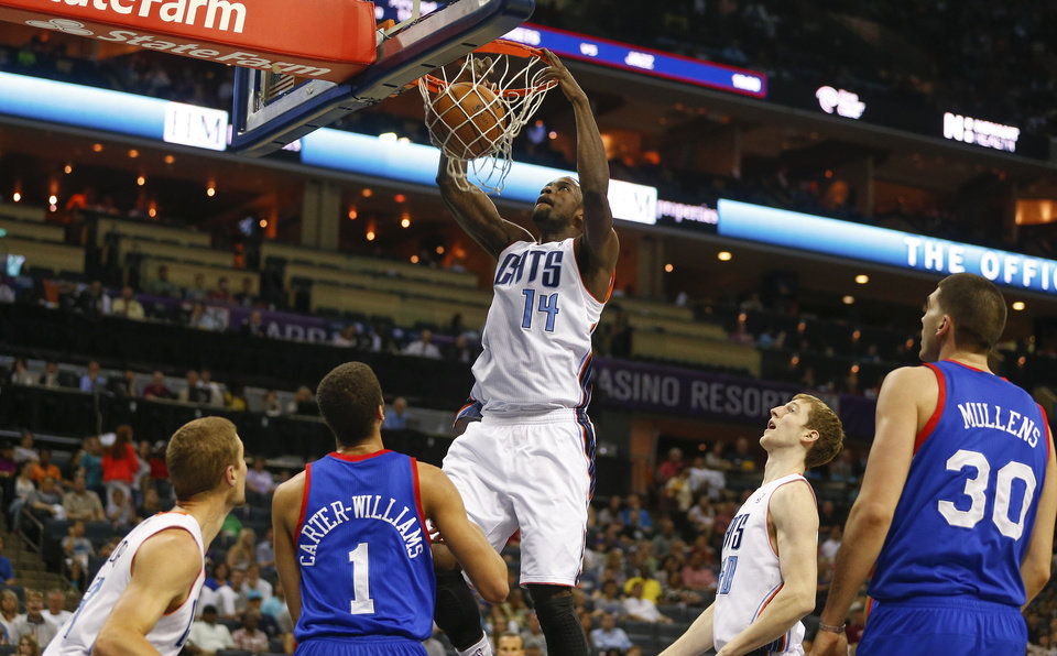 Photo - Charlotte Bobcats forward Michael Kidd-Gilchrist (14) dunks the ball against the Philadelphia 76ers during the first half of an NBA basketball game in Charlotte, N.C., Saturday, April 12, 2014. (AP Photo/Chris Keane)