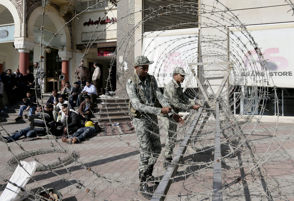 Photo - Supporters of Egyptian president Mohammed Morsi, left, sit as Egyptian Army soldiers lay barbed wire near the presidential palace to secure the site of overnight clashes between supporters and opponents of President Mohammed Morsi in Cairo, Egypt, Thursday, Dec. 6, 2012. The Egyptian army has deployed tanks outside the presidential palace in Cairo following clashes between supporters and opponents of Mohammed Morsi that left several people dead and hundreds wounded. (AP Photo/Hassan Ammar)